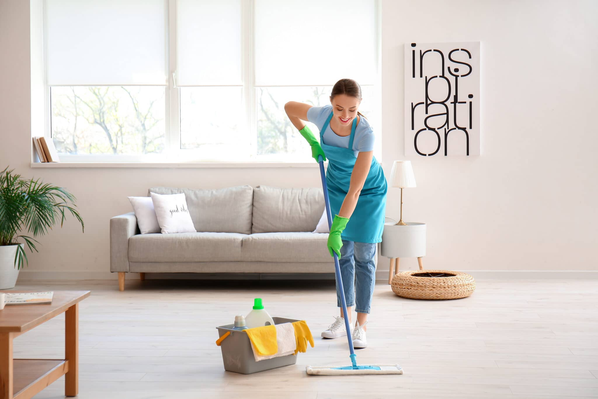 Young woman mopping floor in room